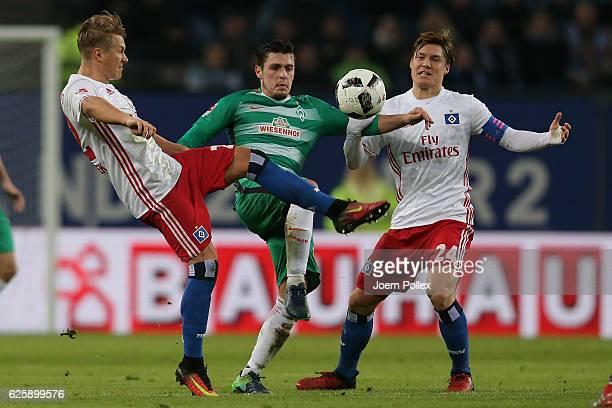 Matthiuas Ostrzolek and Gotoku Sakai of Hamburg and Zlatko Junuzovic of Bremen compete for the ball during the Bundesliga match between Hamburger SV...