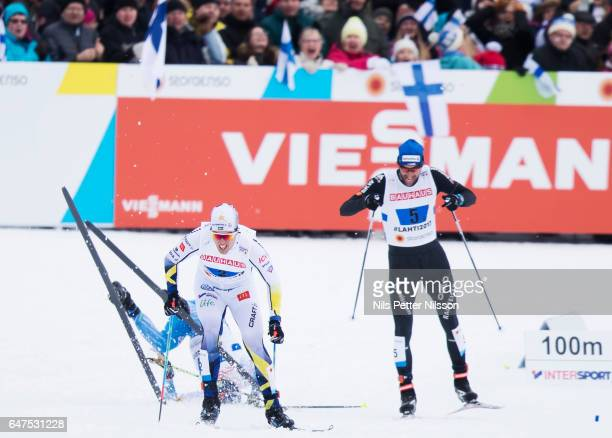 Matti Heikkinen of Finland falls in the last curve as Calle Halfvarsson of Sweden sprints for the bronze medal during the men's cross country relay...