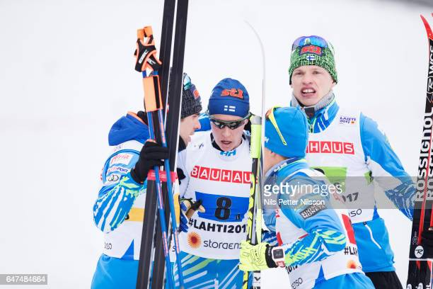 Matti Heikkinen of Finland is comforted by teammates after falling in the last curve during the men's cross country relay during the FIS Nordic World...