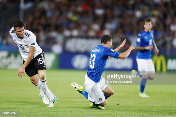 Mattia Caldara of Italy is tackled by MarcOliver Kempf of Germany during the UEFA U21 championship match between Italy and Germany at Krakow Stadium...