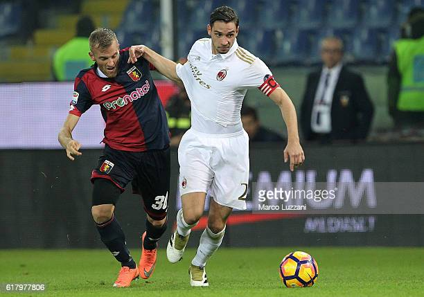 Mattia De Sciglio of AC Milan competes for the ball with Luca Rigoni of Genoa CFC during the Serie A match between Genoa CFC and AC Milan at Stadio...