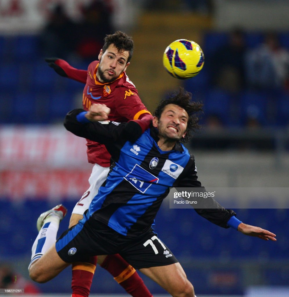Mattia Destro (L) of AS Roma competes for the ball with Cristian Raimondi of Atalanta BC during the TIM Cup match between AS Roma and Atalanta BC at Olimpico Stadium on December 11, 2012 in Rome, Italy.