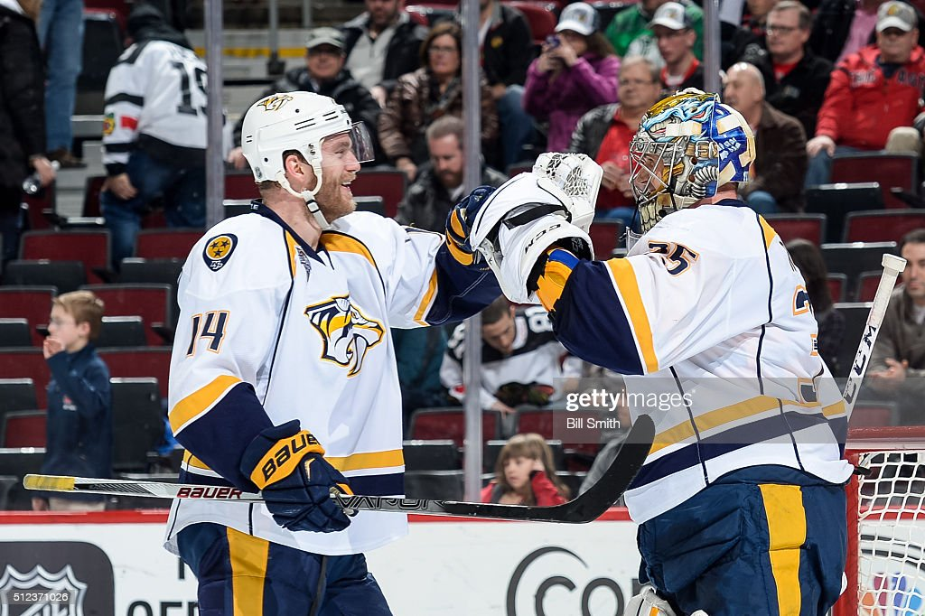 Mattias Ekholm and goalie Pekka Rinne of the Nashville Predators celebrate after defeating the Chicago Blackhawks 3 to 1 during the NHL game at the...