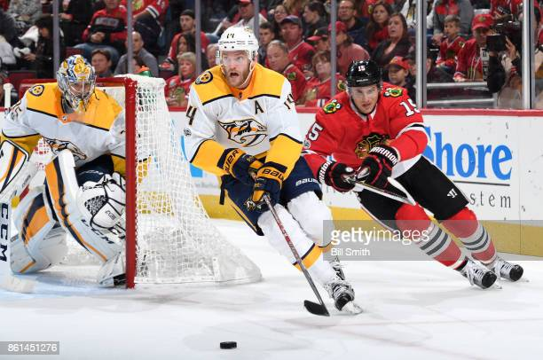 Mattias Ekholm of the Nashville Predators and Artem Anisimov of the Chicago Blackhawks chase the puck around the net guarded by Pekka Rinne in the...
