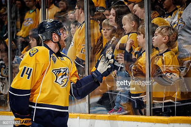 Mattias Ekholm of the Nashville Predators bounces a puck off the glass to the delight of a young fan during warmups prior to an NHL game against the...