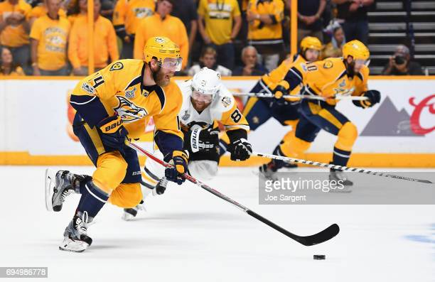 Mattias Ekholm of the Nashville Predators rushes the puck up ice as Phil Kessel of the Pittsburgh Penguins pursues the play in the first period of...