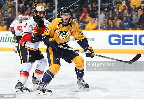 Mattias Ekholm of the Nashville Predators skates against Mikael Backlund of the Calgary Flames during an NHL game at Bridgestone Arena on March 29...
