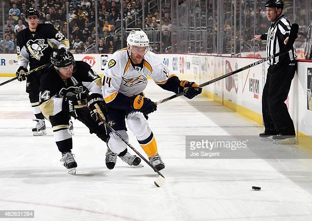 Mattias Ekholm of the Nashville Predators skates for the loose puck alongside Chris Kunitz of the Pittsburgh Penguins at Consol Energy Center on...
