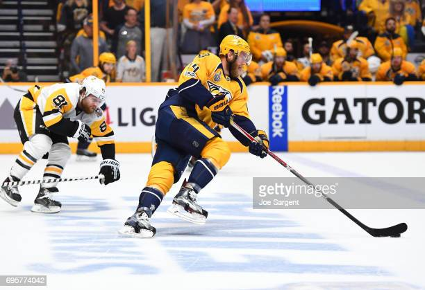 Mattias Ekholm of the Nashville Predators skates the puck out of the defensive zone as Phil Kessel of the Pittsburgh Penguins pursues the play in the...