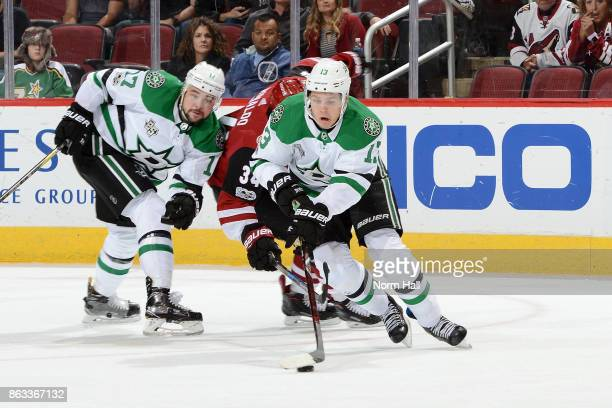 Mattias Janmark of the Dallas Stars skates away with the puck as Devin Shore of the Stars and Zac Rinaldo of the Arizona Coyotes collide during the...