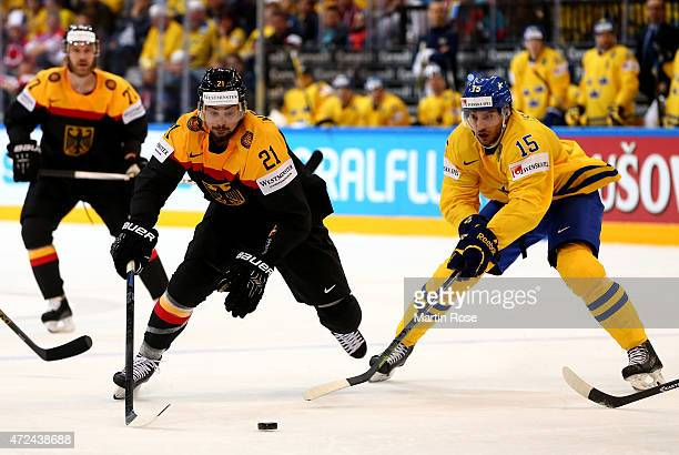Mattias Sjorgen of Sweden and Nicolas Kramer of Germany battle for the puck during the IIHF World Championship group A match between Sweden and...