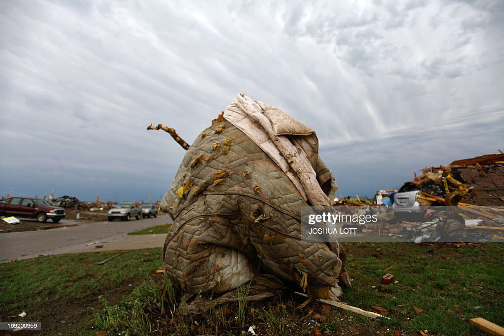 A mattress sits wrapped around a tree outside of a destroyed home on May 21, 2013 in Moore, Oklahoma. Families returned to a blasted moonscape that had been an American suburb Tuesday after a monstrous tornado tore through the outskirts of Oklahoma City, killing at least 24 people. Nine children were among the dead and entire neighborhoods vanished, with often the foundations being the only thing left of what used to be houses and cars tossed like toys and heaped in big piles. AFP PHOTO/Joshua LOTT