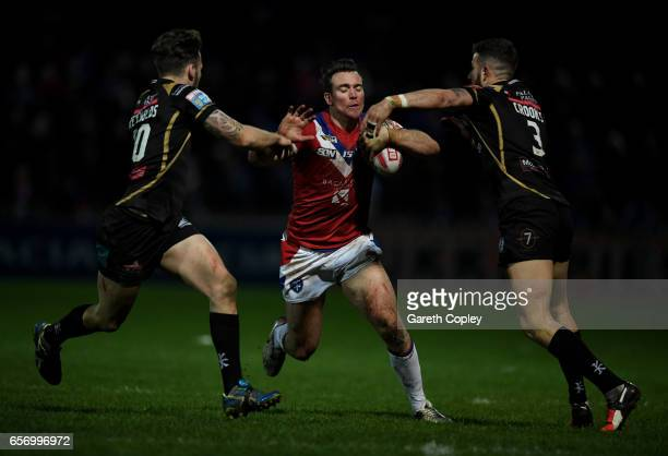 Matty Ashurst of Wakefield is tackled by Ben Reynolds and Ben Crooks of Leighbduring the Betfred Super League match between Wakefield Trinity and...