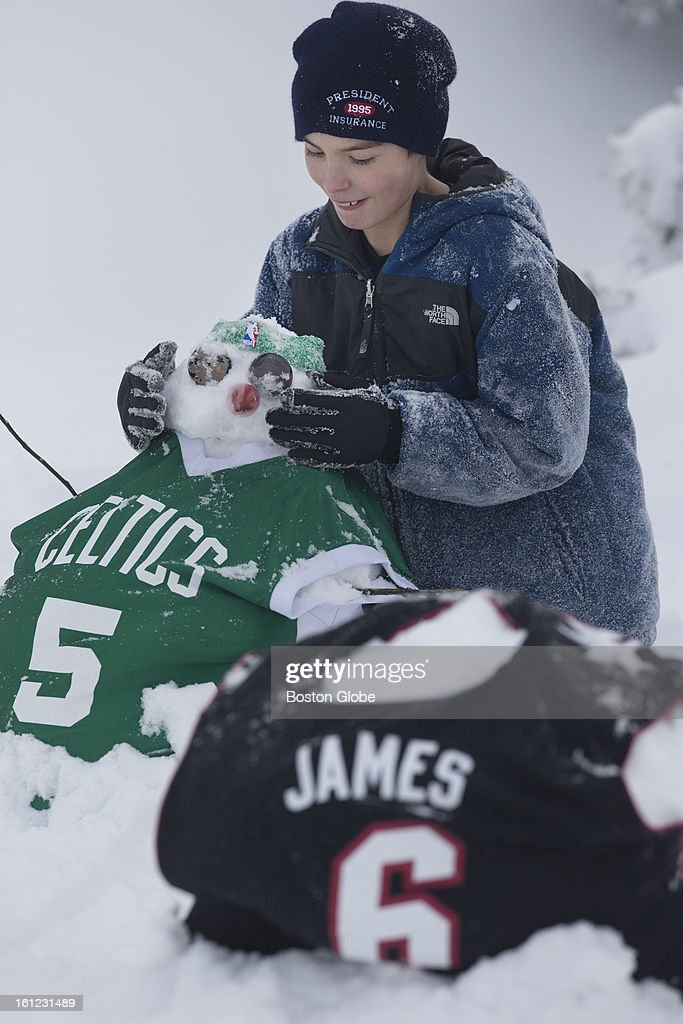 Matty Daubec puts the finishing touches on Kevin Garnett and LeBron James snowmen in Squantum.