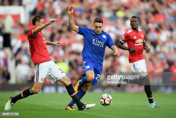Matty James of Leicester City takes the ball past Nemanja Matic of Manchester United during the Premier League match between Manchester United and...
