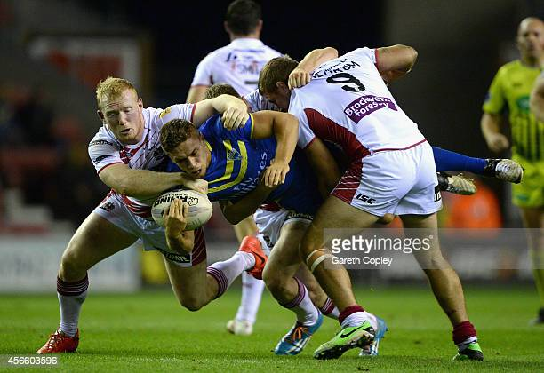 Matty Russell of Warrington Wolves is tackled by Liam Farrell and Michael McIlorum of Wigan Warriors during the First Utility Super League Qualifying...