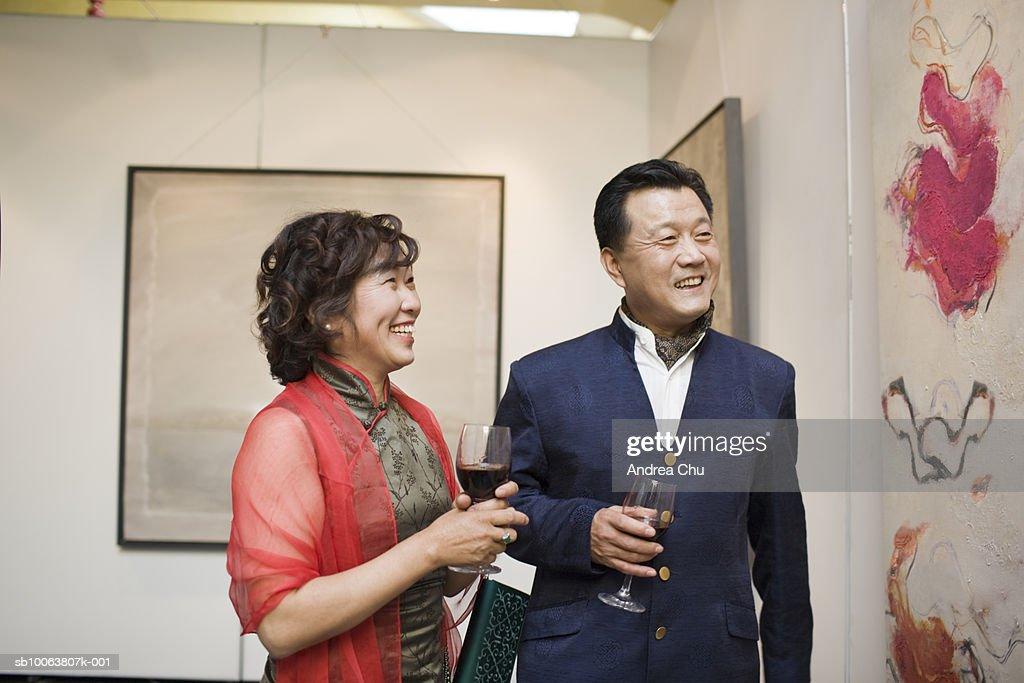 Matue couple holding wine glass, smiling : Stock Photo