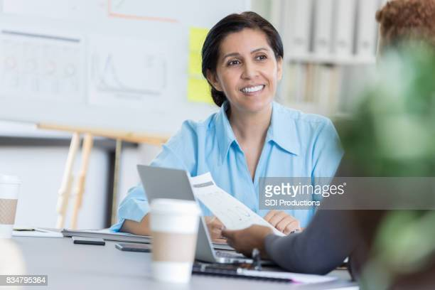 Mature adult businesswoman brainstorms with coworker