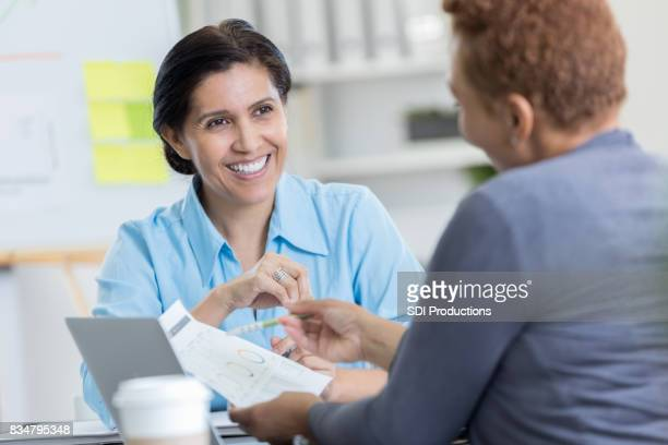 Mature adult businesswoman listens to coworker's new ideas