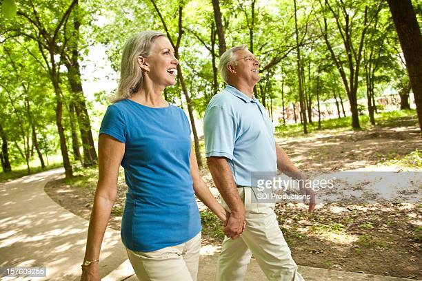 Mature Adult Couple Walking in a Park Trail
