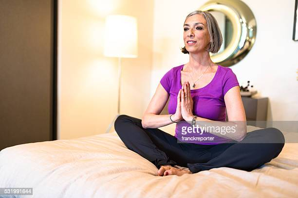 mature adult doing yoga in the bedroom