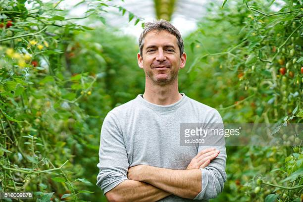 Mature adult entrepreneur standing in his small business greenhouse