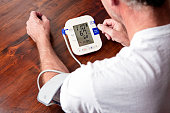 Senior man monitoring his blood pressure at home