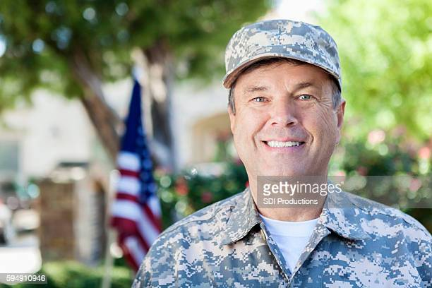 Mature adult soldier in uniform smiling outdoors