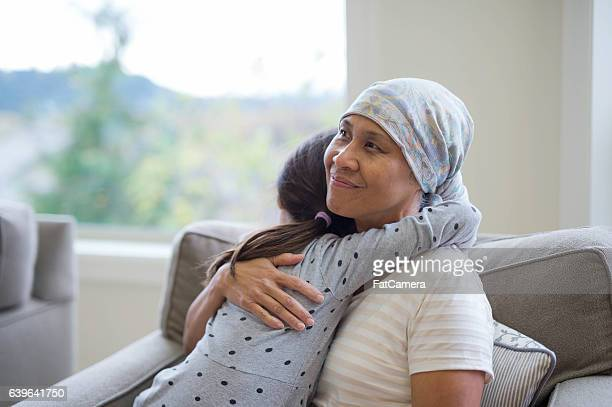 Mature adult with cancer hugging her grandchild