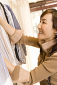 A Mature Adult Woman Choosing Clothes at a Clothes Shop, Side View, Differential Focus