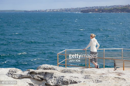 Mature adult woman on cliff-top looking out to sea
