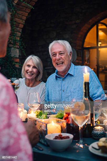 Mature Adults Dining Outdoors by Candlelight