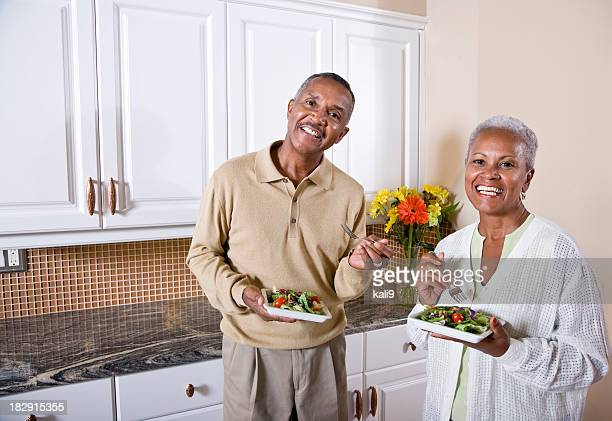 Mature African American couple eating salad in kitchen