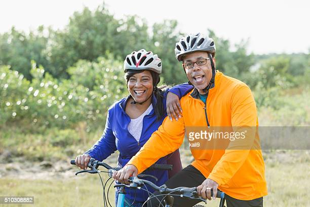 Mature African American couple riding bikes in park