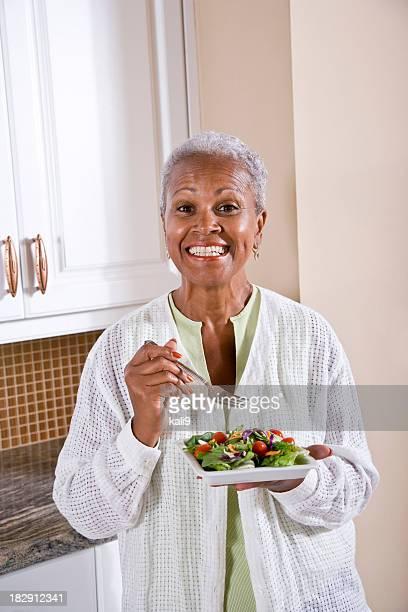 マチュアアフリカ系アメリカ人の女性のサラダを食べキッチン