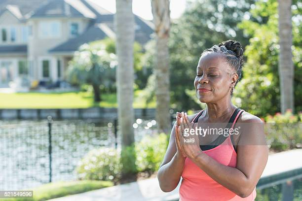Mature African American woman meditating outdoors