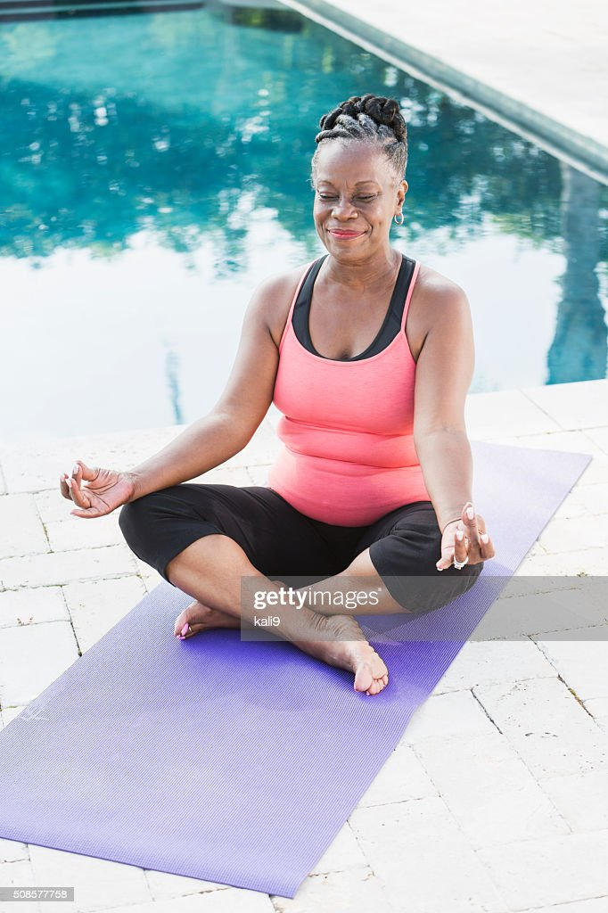 Mature African American woman sitting in lotus position : Stock Photo