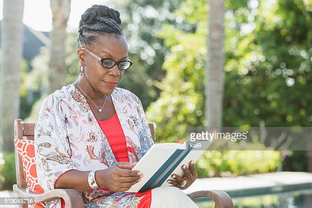 Mature African American woman sitting outdoors, reading