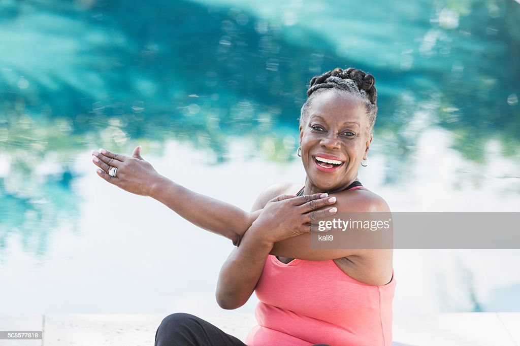 Mature African American woman stretching by pool : Stockfoto