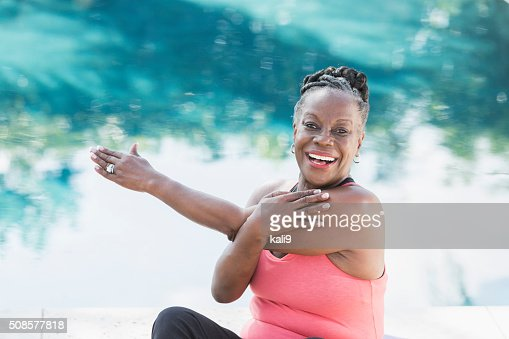 Mature African American woman stretching by pool : Stock Photo