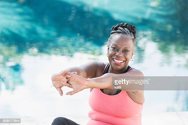 Mature African American woman stretching by pool