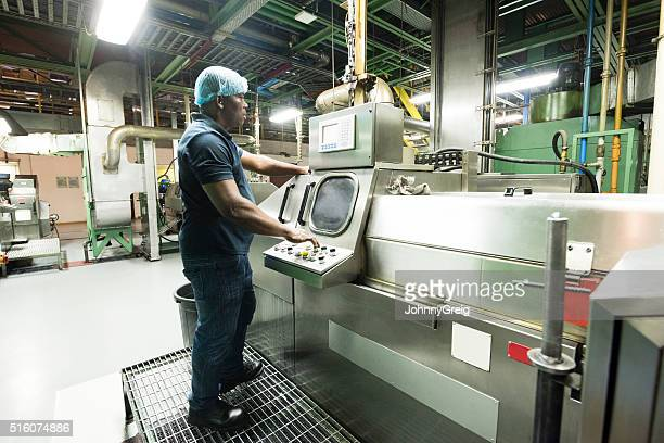 Mature African using control panel in aluminium plant