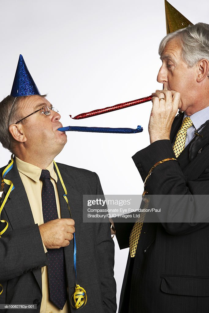 Mature and senior businessman wearing party hats, blowing party blowers : Stock Photo