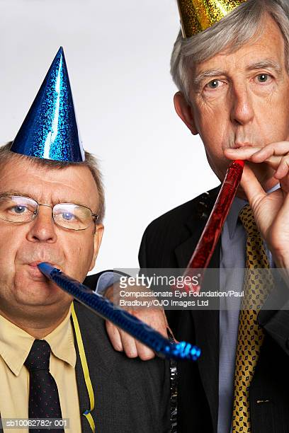 Mature and senior businessman wearing party hats, blowing party blowers, portrait