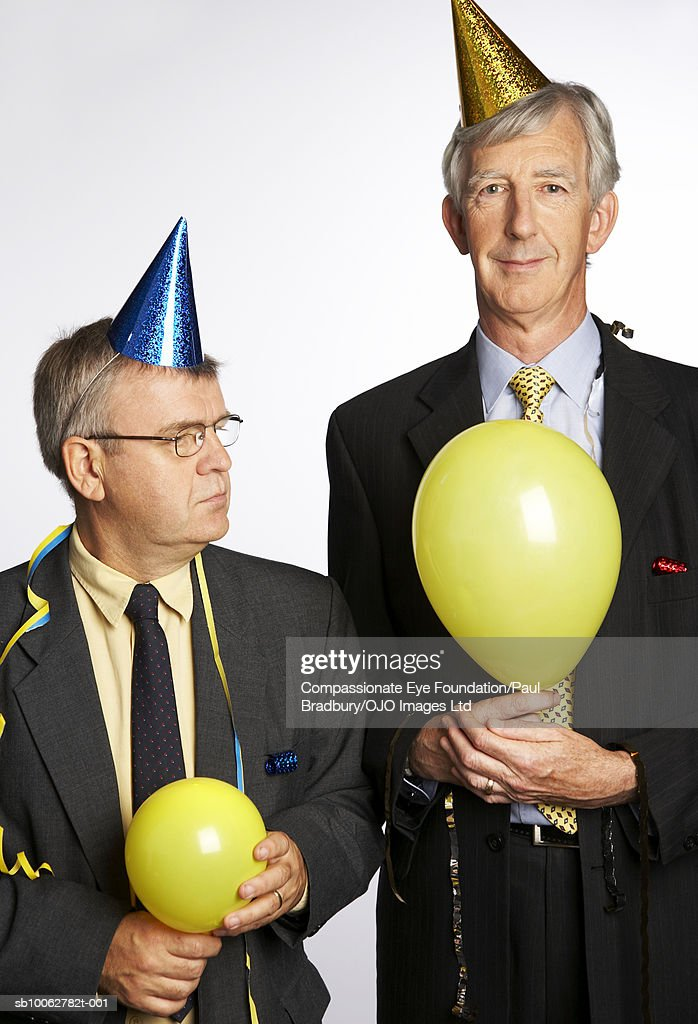 Mature and senior businessman wearing party hats, holding balloons