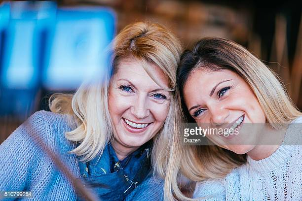Mature and young woman making selfie shot in modern interior