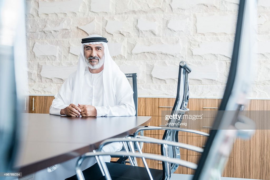 Mature Arab businessman in traditional clothing in modern office