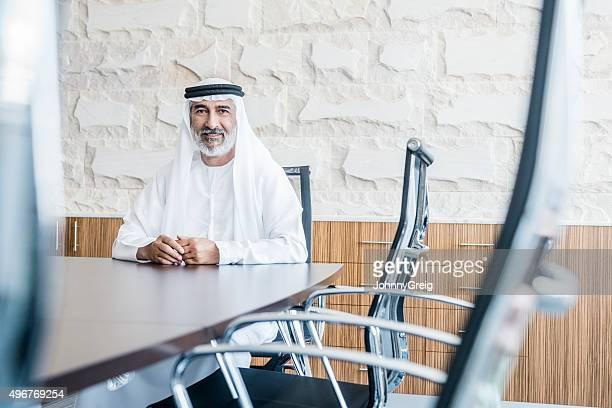 Ältere arabische Geschäftsmann in traditioneller Kleidung in modernen Büro