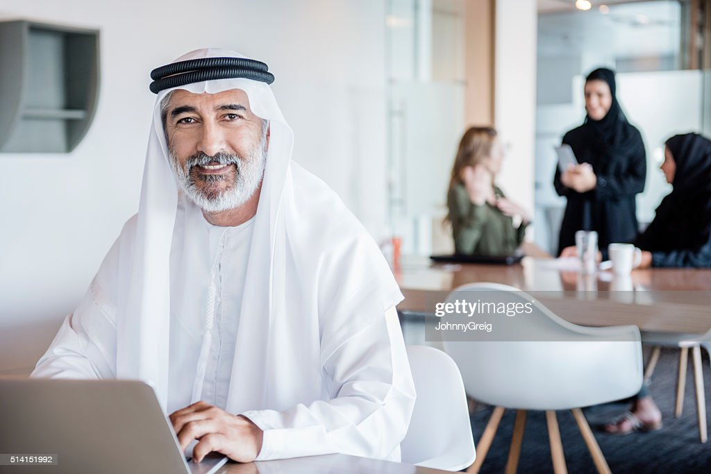 Mature Arab businessman wearing ghutra using laptop, portrait