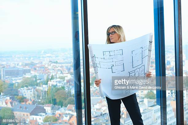 Mature architect in front of office window with Brussels cityscape, Belgium